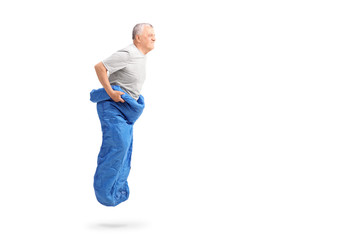 Senior man jumping in a blue sack and smiling