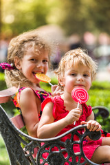 Two happy little girls with lollipops outdoors