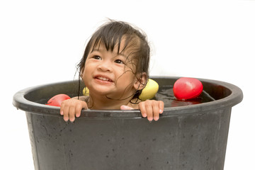 little girl playing with water in little plastic bath tab