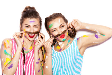 Two lovely painted girl friends having fun