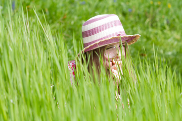 Little girl is playing on green meadow and examining  flower