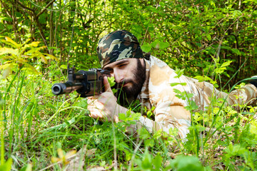 Bearded soldier with a rifle lying in the woods