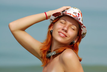 Young smiling redhead woman in hat with closed eyes