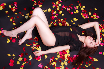 Beautiful young woman laying on sparse rose petals