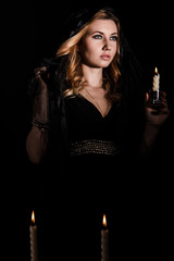 Young woman with a candle in darkness