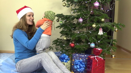 woman play and talk with cute baby girl near Christmas tree