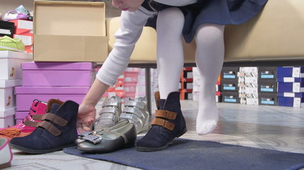girl choosing and trying on new shoes in childrens shoe store