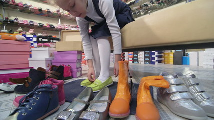 Child  trying on new shoes for girls in children shoe store