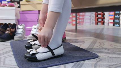 school girl trying on new  flat shoes in children shoe store
