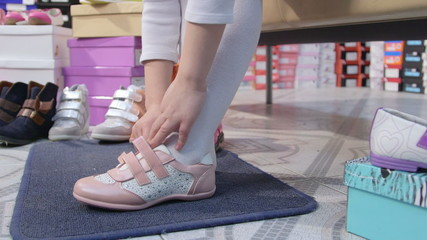 Child trying on sneakers for girls in  shoe store