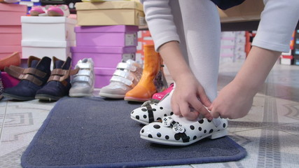 Little girl  trying on new  flat shoes in children shoe store