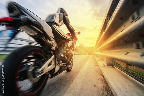 Moto da strada sfreccia vicino al rambarde al tramonto Poster