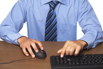 Businessman in blue shirt typing on computer keyboard