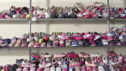 Shelf  with shoes for kids in the children shoe store pan shot