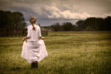 Girl wearing a dress walking in a pasture