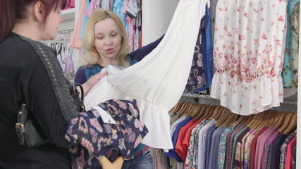 Woman looking for summer pregnancy clothing in baby store