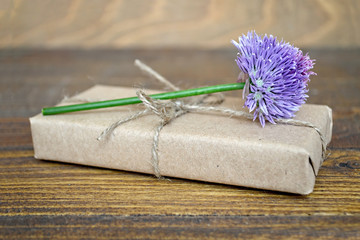 Parcel  wrapped in brown paper and chive flower