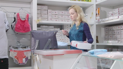 Young pregnant woman buying pregnancy hospital bag and clothes