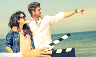 Young couple in love acting for romantic film at beach