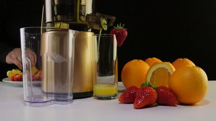 Making  fruit juice strawberry  orange using masticating juicer