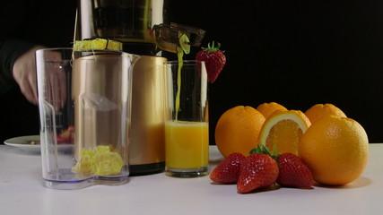 Making fresh fruit juice strawberry orange using juicer