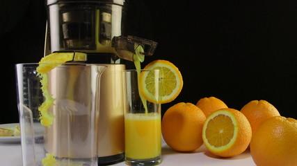 Making fresh fruit juice from orange using  cold press juicer