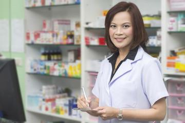 pharmacist woman standing in pharmacy drugstore