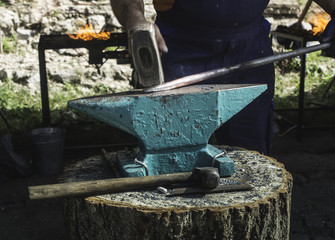 Blacksmith forges iron on anvil