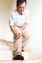 Matured man suffering acute knee joint pain descending stairs
