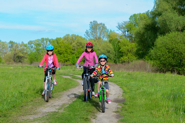 Mother and kids on bikes cycling outdoors, family sport