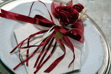 Bomboniera con nastro rosso e rosa su piatto argento