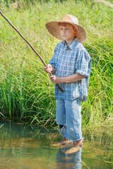 Barefoot angler boy fishing standing in freshwater