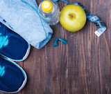 neakers, water, towel and earphones on the wooden background