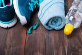 Sneakers, water, towel and earphones on wooden background