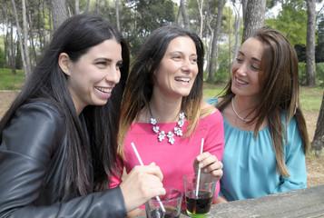 Three ypung women smiling and talking