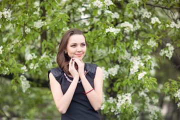Girl in black standing on a blooming lilac backgroud