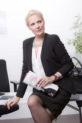 Attraktive Geschäftsfrau sitzt auf Schreibtisch