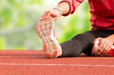 Runner feet running on running track closeup on shoe