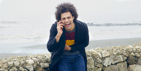 Handsome man laughing on the phone in front of the ocean