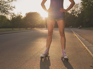 Young woman wearing roller skates in park at sunset