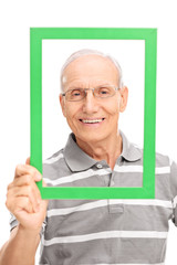 Senior man holding a green picture frame
