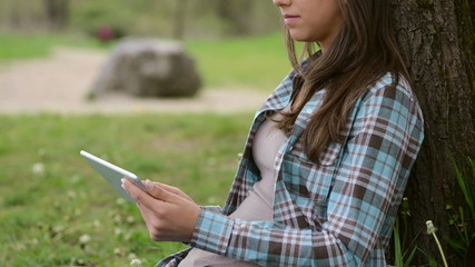 Beautiful girl at the park using a tablet