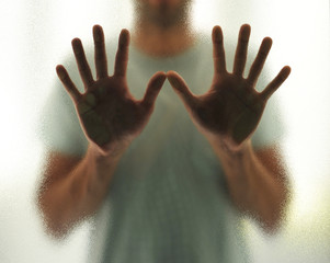 Young man with outstretched hands behind the glass