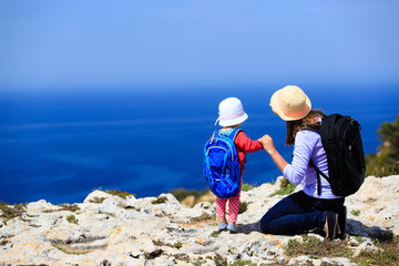 mother with little daughter travel in mountains