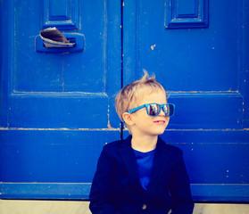 cute little boy outdoors against blue door