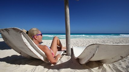 Woman relaxing  on beach with sun umbrellas and beds