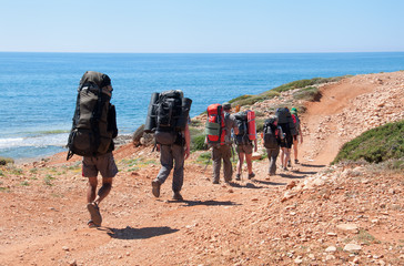 group of tourists with large backpacks are on road to the sea