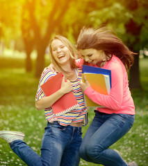 Happy students in summer park jumping of happines
