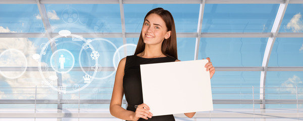 Smiling young businesswoman holding blank paper