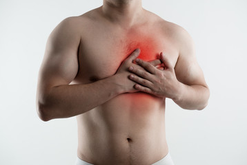 Heart attack. Closeup of male torso with red point on his chest